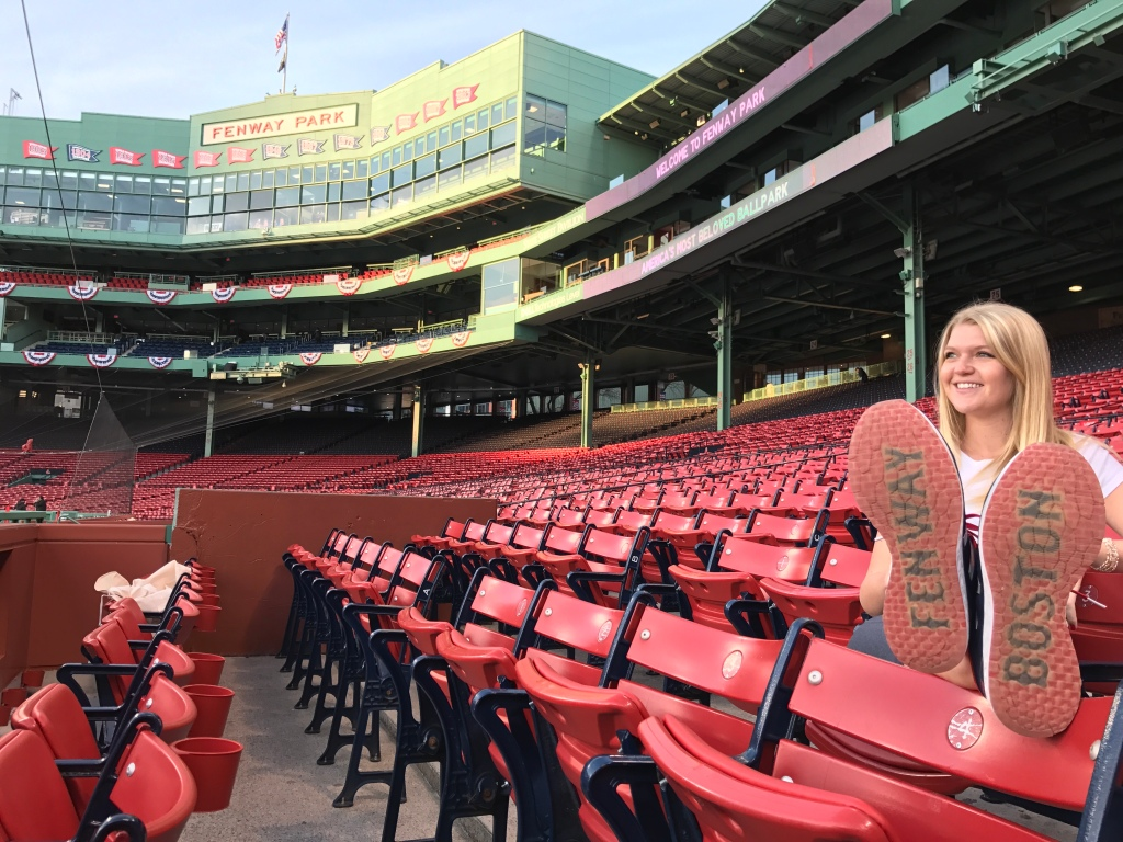 """Kailee at Fenway with her feet up and shoes that say """"Fenway"""" and """"Boston"""""""